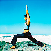 side view of a young woman doing yoga at the beach