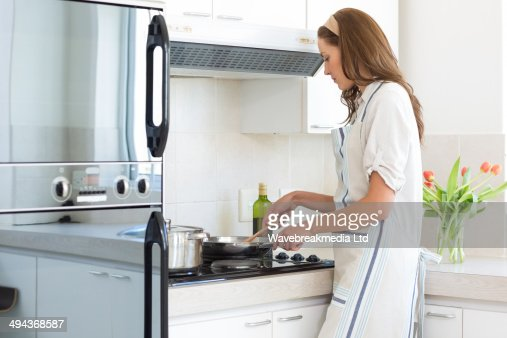 Side view of woman preparing food in kitchen : Foto stock