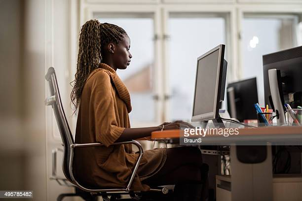 Side view of African American businesswoman using desktop PC.