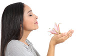 Side view of an arab woman smelling a flower isolated on a white background