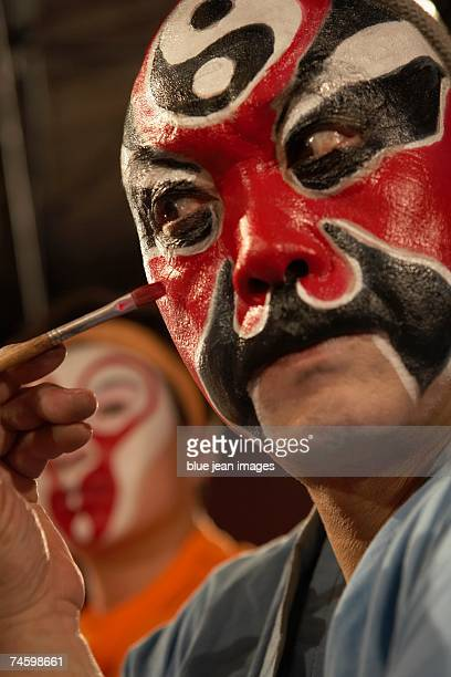 Side view of an old actor as he carefully applies traditional Chinese face paint under his eye.