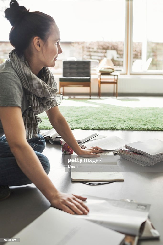 Side view of architect working on floor at home office