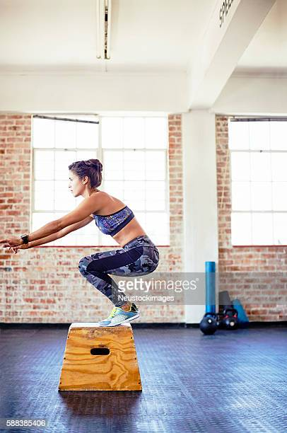 Side view of athlete is crouching on box in gym
