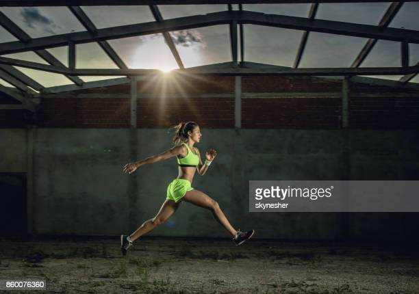 Side view of athletic woman jumping in a run at old warehouse.