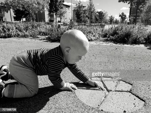 Side View Of Baby Boy Playing On Road