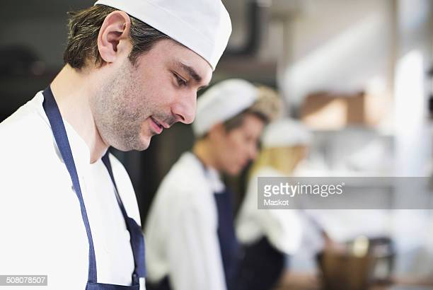 Side view of baker in kitchen at bakery