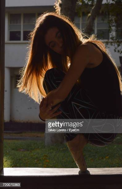 Side View Of Ballet Dancer Hugging Knees While Balancing With Tiptoes On Window Sill