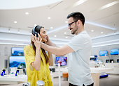 Side view of beautiful young stylish adorable love couple testing headphones in a tech store.