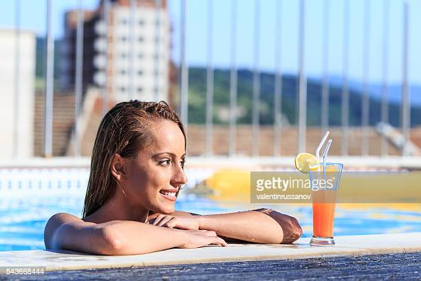 Side view of beautiful young woman drinking cocktail on pool