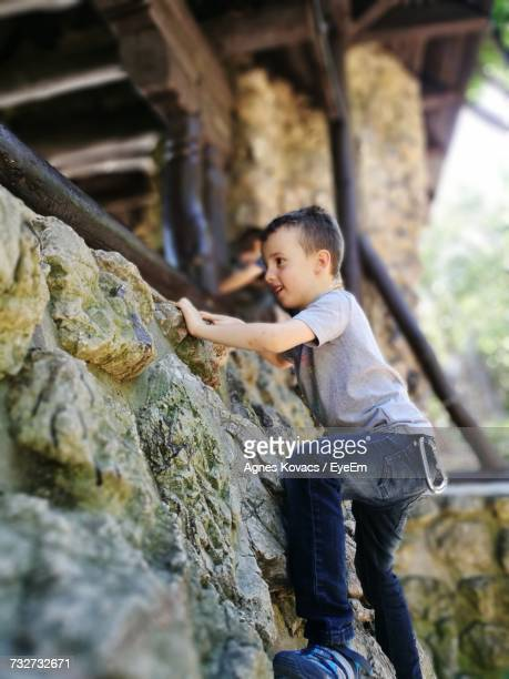 Side View Of Boy Climbing On Stone Wall