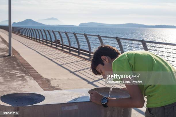 Side View Of Boy Drinking Water From Fountain While Standing By Railing Against Sea