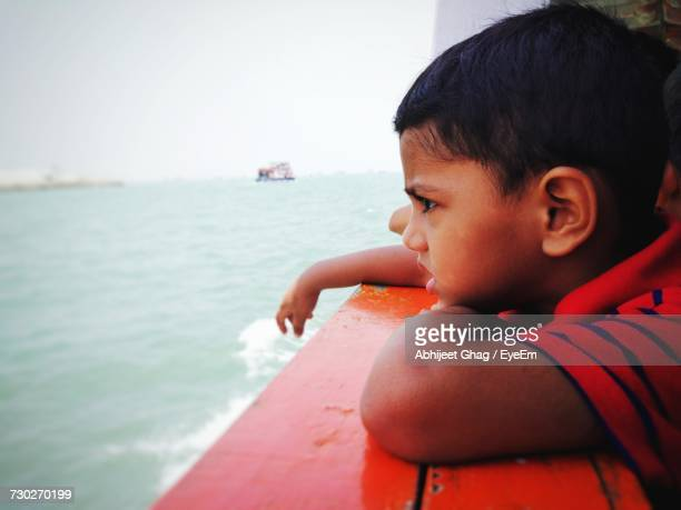 Side View Of Boy Looking At Sea From Boat