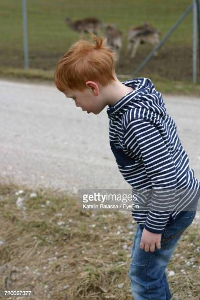Side View Of Boy Looking Down While Standing On Grassy Field By Road