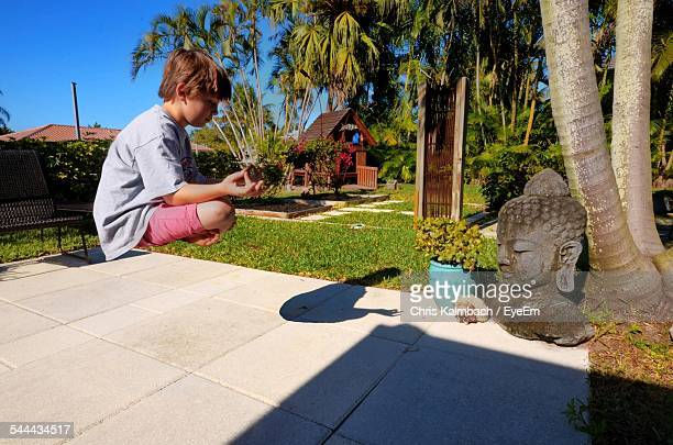 Side View Of Boy Meditating In Front Of Buddha Statue In Park