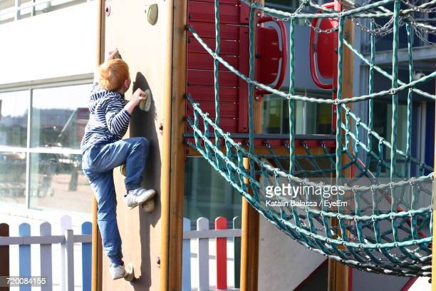 Side View Of Boy Playing At Playground On Sunny Day
