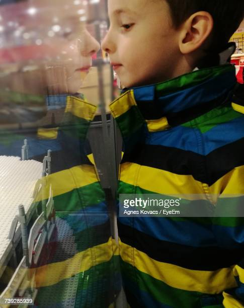 Side View Of Boy Reflecting On Glass At Exhibition Center