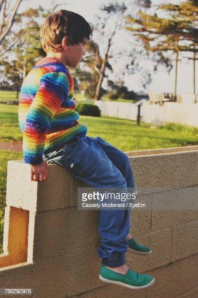 Side View Of Boy Sitting On Retaining Wall