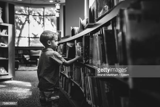 Side View Of Boy Standing By Bookshelf In Library