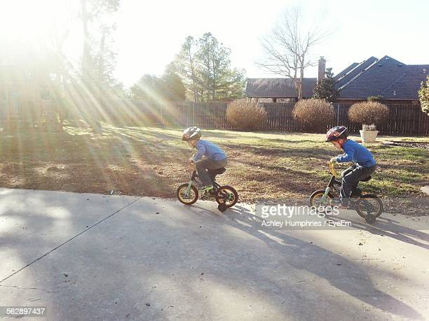 Side View Of Boys Riding Bicycle In Back Yard