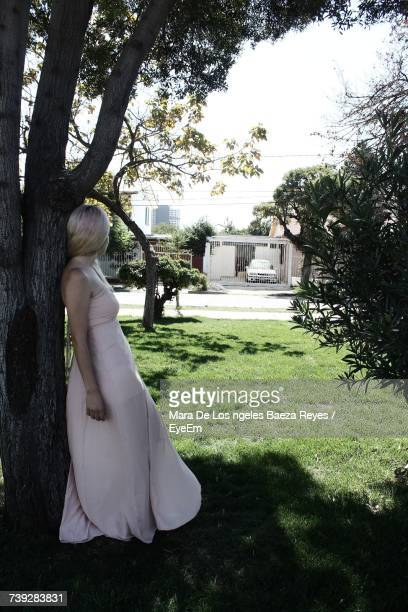 Side View Of Bride Leaning On Tree While Standing Outdoors