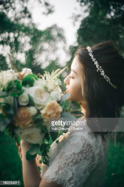 Side View Of Bride With Bouquet Standing On Field
