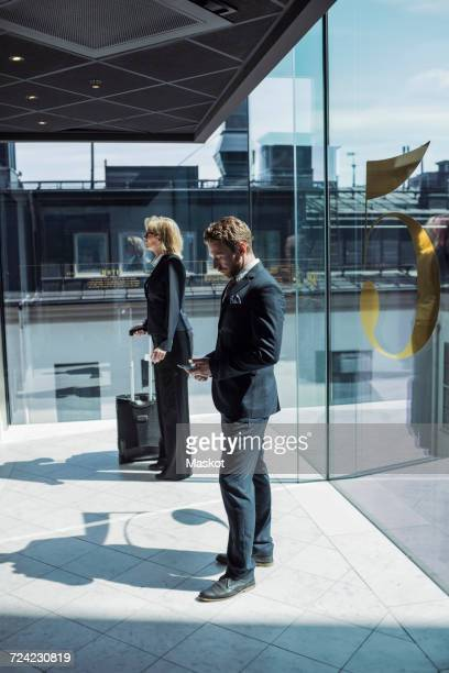 Side view of business people standing in hotel corridor