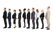 Full length side view of business team standing in row against white background