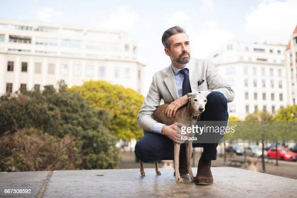 Side view of businessman crouching by dog at doorway