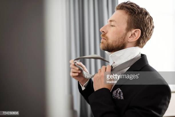 Side view of businessman fastening necktie against window in hotel room
