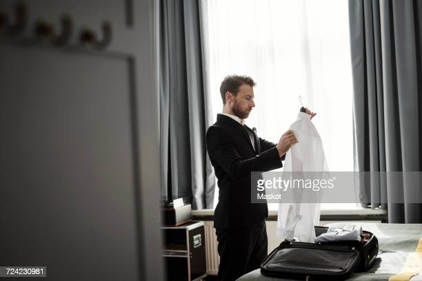 Side view of businessman holding white shirt in coathanger at hotel room