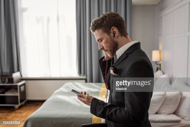Side view of businessman listening to mobile phone in hotel room