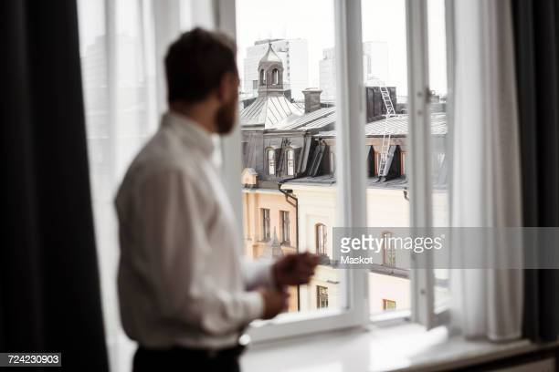 Side view of businessman looking at buildings through window from hotel room