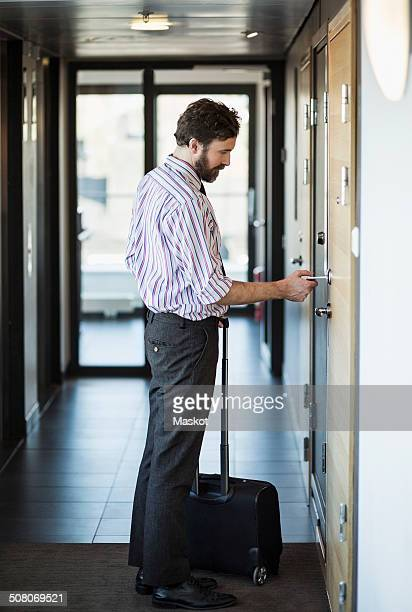 Side view of businessman opening hotel door with cardkey
