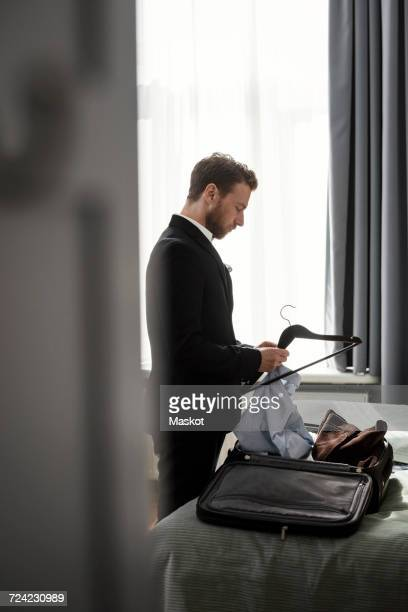 Side view of businessman positioning shirt on coathanger in hotel room
