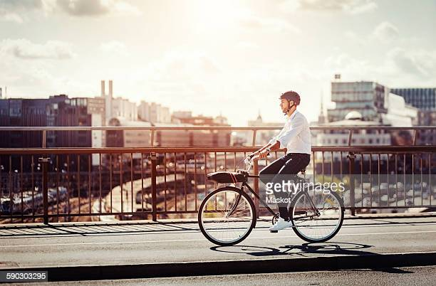 Side view of businessman riding bicycle on bridge in city