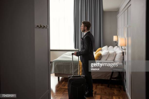 Side view of businessman standing with luggage by bed in hotel room