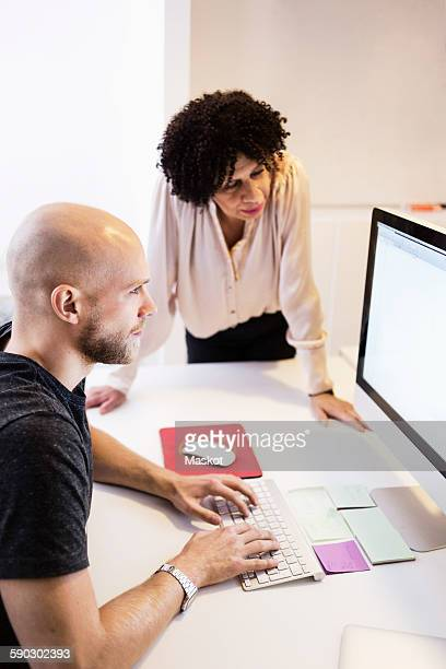 Side view of businessman using computer while colleague looking at it in office