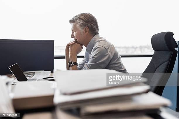 Side view of businessman using laptop at desk in office