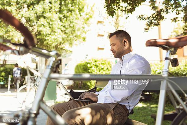 Side view of businessman using laptop while sitting on park bench