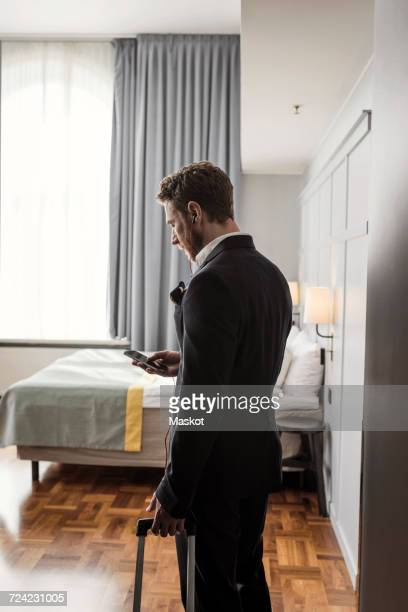 Side view of businessman using mobile phone standing with luggage in hotel room