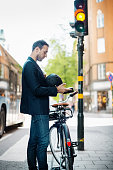 Side view of businessman using mobile phone while standing with bicycle on city street