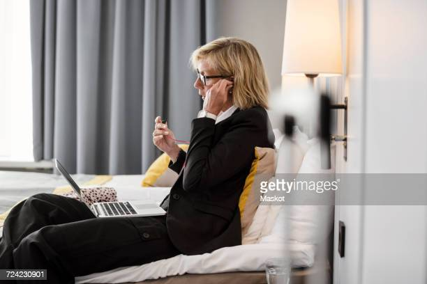 Side view of businesswoman adjusting headphones using laptop on bed at hotel room