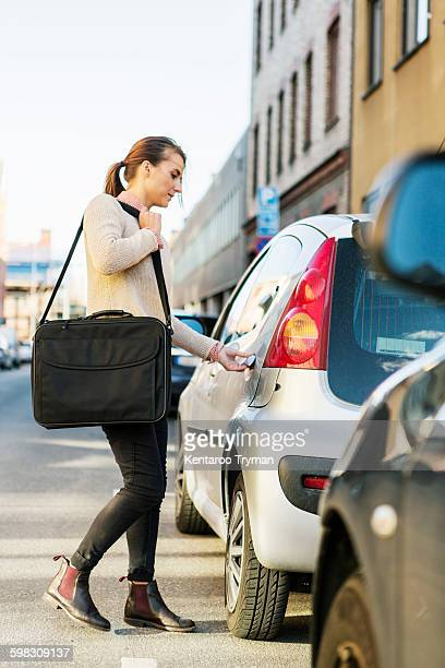 Side view of businesswoman entering car on street