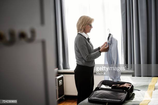 Side view of businesswoman holding shirt against window at hotel room