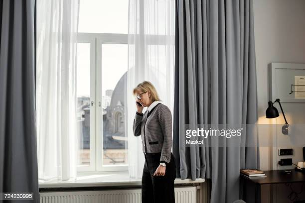 Side view of businesswoman listening to mobile phone standing by window at hotel room