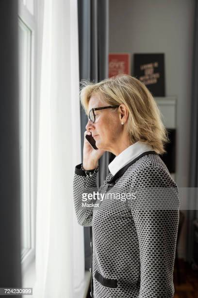 Side view of businesswoman listening to smart phone while looking through window at hotel room