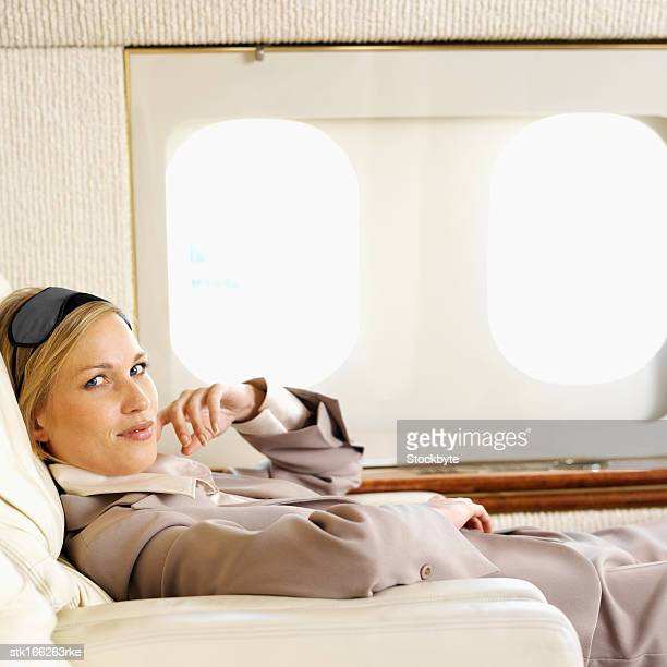 side view of businesswoman relaxing in first class airplane