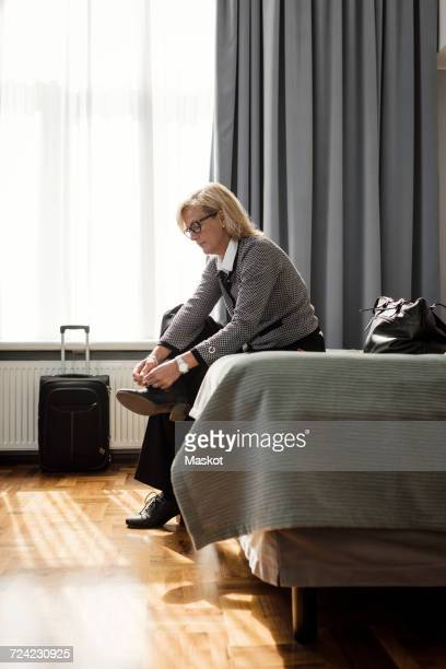 Side view of businesswoman tying shoelace sitting on bed at hotel room