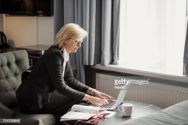 Side view of businesswoman using laptop by window at hotel room