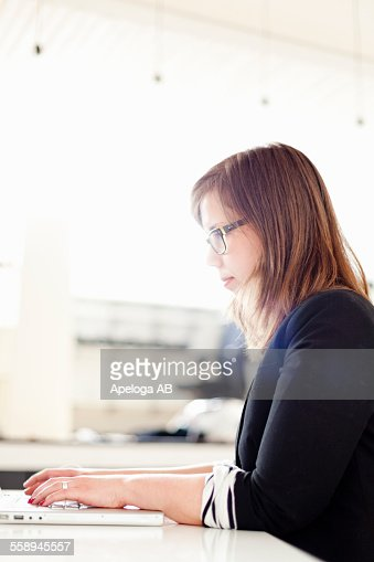 side view of businesswoman using laptop in office stock foto getty images. Black Bedroom Furniture Sets. Home Design Ideas